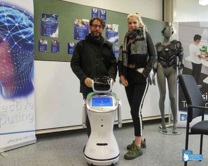 Two persons are standing together with a robot.